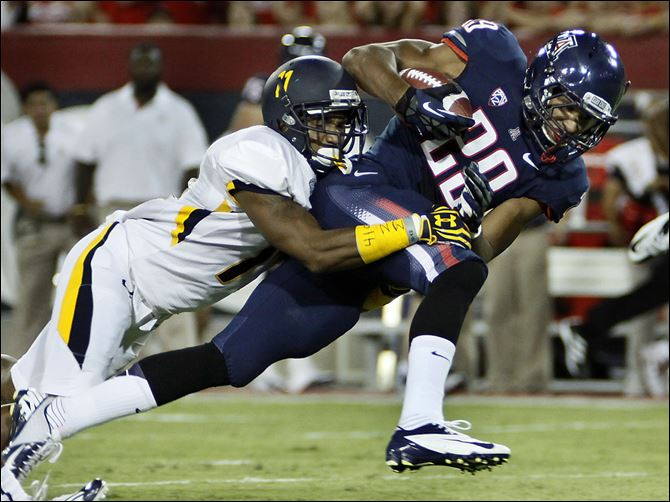 Toledo Arizona Football Arizona's Austin Hill (29) tries to break the tackle of Toledo's Cheatham Norrils, left, during the first half of Saturday night's game.