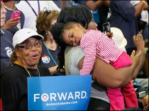 A'Nyah, 2, held by mother Jasmine Wallace, sleeps before the arrival of Mr. Obama. Alfreda Bailey is at left.