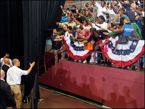 Mr. Obama says goodbye to the public as he exits Scott High School's gymnasium.