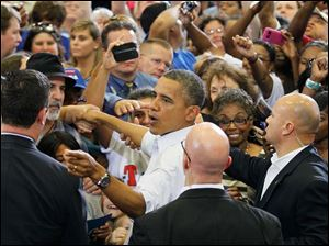 President Obama greets the crowd as he leaves Scott High School.