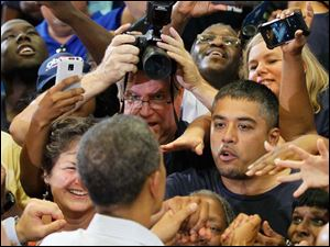 Those not within reach to shake the President's hand try to capture a photo of him as he walks by.
