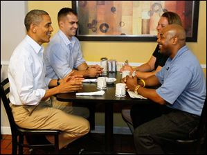 President Obama  talks with auto workers Daniel Schlieman, back left, Heather Finrock, and James Fayson, right, at Rick's City Diner.