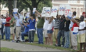 Supporters of Republican presidential candidate Mitt Romney greet President Obama as he arrives at Scott High School.