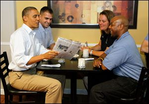 President Barack Obama looks at a copy of the Blade while sitting in Rick's City Diner in Toledo  with Daniel Schlieman, back left, Heather Finrock, and James Fayson, right.