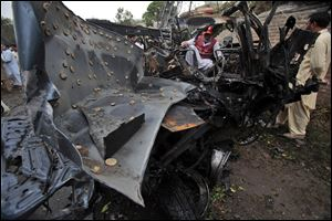 A Pakistan rescue worker looks at a vehicle targeted by terrorists in Peshawar, Pakistan on Monday, Sept. 3, 2012.  A suicide bomber rammed a car filled with explosives into a U.S. government vehicle in northwestern Pakistan Monday.