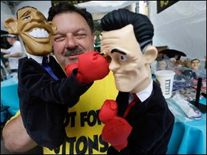 Street Vendor Mark Evans shows off his Obama and Romney hand puppets during Carolina Fest.