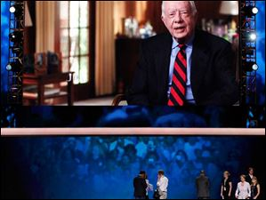 House Minority Leader Nancy Pelosi of California walks across the stage under a large television picture of former President Jimmy Carter.
