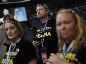Teamsters supporters Libby Conrad, left, Randy Conrad and Dixie Pope from Kernersville, N.C., watch as First Lady Michelle Obama appears at the lectern for a camera test on the stage at the Democratic National Convention inside Time Warner Cable Arena.