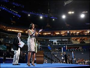 First Lady Michelle Obama gestures as she appears at the podium for a camera test on the stage.