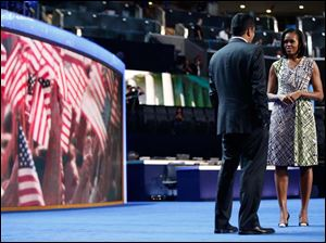 First Lady Michelle Obama appears on the stage with actor Kal Penn for filming a campaign video.