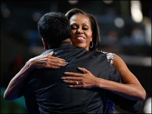 First Lady Michelle Obama hugs actor Kal Penn after filming a campaign video.