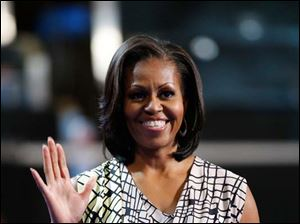 First Lady Michelle Obama waves as she appears on the stage to film a campaign video at the Democratic National Convention.