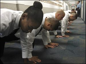 Marquitta Bey, foreground, joins other recruits in doing pushups in the hallway at the Toledo Police Academy law enforcement building at Owens Community College on the first day of training.