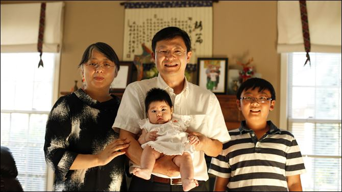 Sam Yang, holding  daughter Lydia, is joined by his wife, Ying Li, and son Evan in their Perrysburg home. Mr. Yang, a research and development manager at First Solar Inc., would like to see more facilities in the area for Chinese and Chinese-Americans.