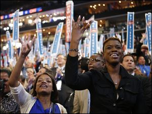 Delegates cheer as First Lady Michelle Obama addresses the Democratic National Convention.