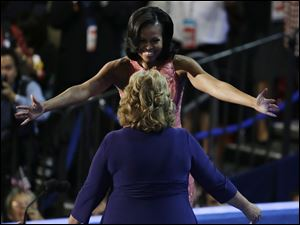 First Lady Michelle Obama hugs Elaine Brye before speaking.