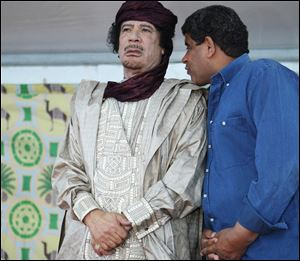 Intelligence chief Abdullah al-Senoussi, right, whispers to Libyan leader Moammar Gadhafi in Sabha, Libya. A government statement read on national radio states that Mauritania has agreed to extradite Moammar Gadhafi's former spy chief, months after he tried to slip into Mauritania wearing a disguise and