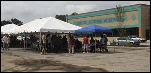 Students of Horizon Science Academy attend orientation under two tents in the parking lot of DeVeaux Village on Tuesday. The City of Toledo denied an occupancy permit to the building last week.