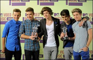 Members of the British band One Direction, from left, Louis Tomlinson, Liam Payne, Harry Styles, Zayn Malik and Niall Horan pose backstage with their awards at the MTV Video Music Awards.
