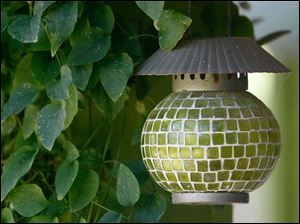 A candle holder blends with the surrounding greenery.