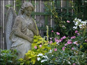 An angel looks down on a mix of petunias, impatiens and phlox.