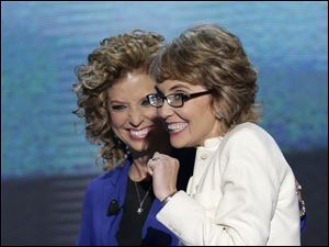 Former Rep. Gabrielle Giffords, right, smiles with Democratic National Committee Chairwoman Rep. Debbie Wasserman Schultz of Florida after reciting the Pledge of Allegiance at the Democratic National Convention.