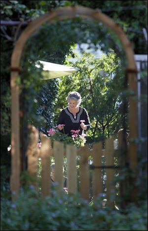 Janice Trudeau is reflected in a cleverly placed mirror, which adds depth to her garden.