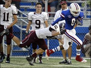 Springfield's JeSean Fisher makes a catch for a first down as Rossford's Sean McCormick makes the tackle in Friday night's game.