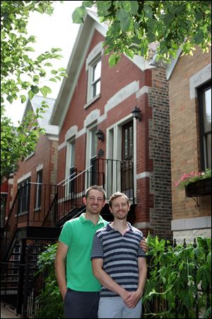 Brian McCord, left, and Jamie Blondin stand outside their Chicago flat. When the couple saw other buyers touring the home with a tape measure, they offered 96 percent of the $649,000 asking price.