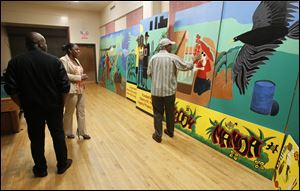 At the Frederick Douglass center, Warren Woodberry, right, shows the mural he helped design. It was painted mostly by residents of the Moody Manor apartments, where gunfire killed a girl, 1, and injured her sister, 2. The mural is to be installed at Moody Manor.