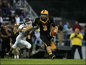 Kyle Kremchek, QB for Northview Wildcats, tries to avoid being tackled by Lake Flyers' Dustin Perkins during the first quarter of their game at Northview High School in Sylvania Township, Ohio, on Saturday.