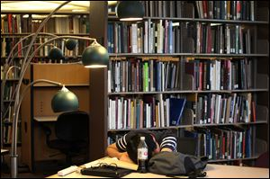 Taewon Kim, an electrical engineering systems graduate student, sleeps in the library at the Duderstandt Center on the campus of the University of Michigan in Ann Arbor.