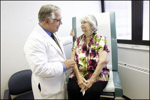Dr. Michael G. Moront of Promedica Toledo Hospital goes through the first follow-up visit with heart valve replacement surgery patient Barbara Streight.