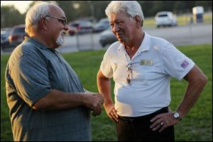 Steve Heer of Lambertville, left, talks with Bedford Township Supervisor Walt Wilburn. The incumbent, who lost the GOP primary, explained the procedures for voting for write-in candidates.