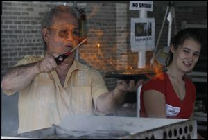 John Skiadas makes saganaki flaming cheese. The festival remains in full swing today from noon to 7 p.m.