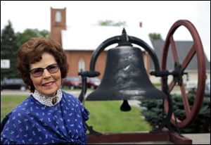 Trudy Urbani, past president of the Historical Society of Bedford, with the bell from First Wesleyan Methodist Church, says it is important to keep history alive for future generations.