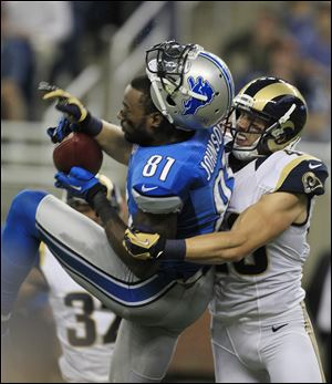 Lions receiver Calvin Johnson loses his helmet after being tackled by St Louis' Craig Dahl. Johnson had 111 yards receiving.