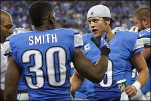 Detroit Lions running back Kevin Smith, left, receives congratulations from quarterback Matthew Stafford after scoring the game-winning touchdown in the fourth quarte rSunday in Detroit. Stafford  threw three first-half interceptions, but in the end, he made the difference for the Lions.