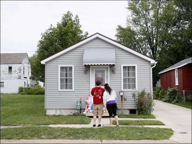Friends Carrie Greenman, right, and David, (who did not want to use his last name), left, stand in front of the home of Heather Jackson, 23, who was found murdered in her home on John Street in Sandusky. Her 3-year-old daughter and 18-month-old son were also found dead at the scene.