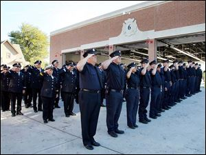 Firefighters salute as the flag is raised during a 9/11 Commemoration Ceremony and Dedication of Fire Station 6 at 1155 Oak Street, Tuesday, September 11, 2012.