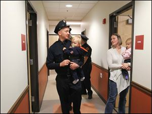 Private Brian Barchick, left, his wife Christine Barchick and their 23-month-old twins Tommy and Ellie take a tour of what will be his new living quarters during a 9/11 Commemoration Ceremony and Dedication of Fire Station 6 at 1155 Oak Street, Tuesday, September 11, 2012.