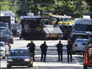 A police armored vehicle advances toward the house in West Bloomfield Township in which the officer died.