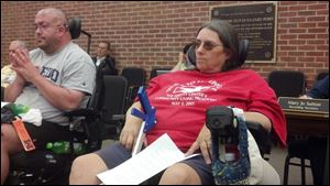 Ernie Brancheau, left, and Deb Angel, clients of public transportation that accommodates people with disabilities, attend the Perrysburg City Council meeting on Tuesday, in city council chambers in Perrysburg. Ms. Angel also is a TARTA board member.