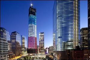 The tower known as 1 World Trade Center, left, the National September 11 Memorial, bottom left, and 4 World Trade Center, right, are bathed in light, Tuesday, in New York.