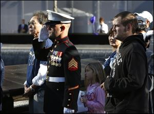 A US Marine salutes as he and others stand at the north reflecting pool of the World Trade Center Memorial during a moment of silence.