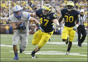 University of Michigan players Jake Ryan (47) and Thomas Gordon (30) can't keep up with Air Force's Cody Getz as he heads for the end zone to score in the fourth quarter on Saturday.