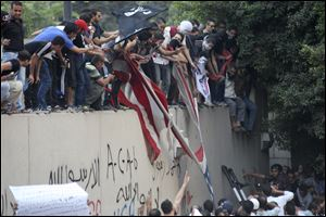 Protesters destroy an American flag pulled down from the U.S. embassy in Cairo, Egypt. Egyptian protesters, largely ultra conservative Islamists, have climbed the walls of the U.S. embassy in Cairo, went into the courtyard and brought down the flag, replacing it with a black flag with Islamic inscription, in protest of a film deemed offensive of Islam.