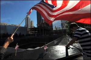 An American flag flies over a man pausing near a reflecting pool at the National September 11 Memorial during the observance of the 11th anniversary of September 11 in New York.