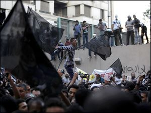 Egyptian protesters climb the walls of the U.S. embassy while others chant anti U.S. slogans during a protest in Cairo, Egypt, Tuesday.