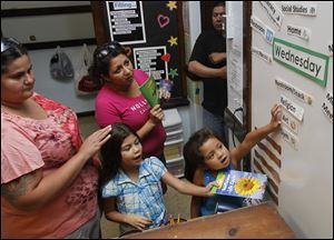 Adriana Borjas, left, stands next to her daughter Reina Conejo, 7, Felicia Guel, center, and her daughter Mya, 6, as they participate in the open house at the Queen of Apostles School in Toledo.